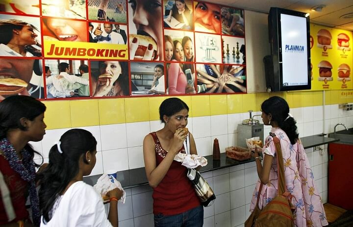 Young Indian women eat the popular food snack vada pav at a Jumbo King food outlet in Mumbai