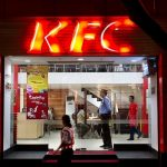 A pedestrian walks past a KFC restaurant in Kolkata, India