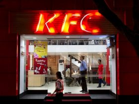 A pedestrian walks past a KFC restaurant in Kolkata, India
